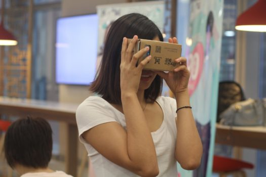 Young woman using a cardboard virtual reality viewer. (Image courtesy AliBaba.)
